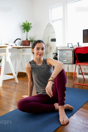 Portrait confident young Latinx woman on yoga mat in apartmentの写真素材 [FYI02336904]