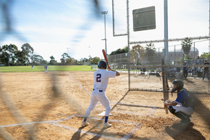 Baseball player at bat on sunny fieldの写真素材 [FYI02336912]