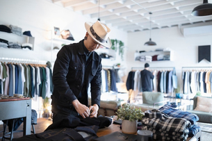 Male business owner arranging display in menswear clothing shopの写真素材 [FYI02336984]