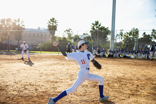 Baseball pitcher throwing the ball on sunny fieldの写真素材 [FYI02337037]