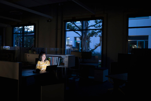 Businesswoman working late at laptop in dark officeの写真素材 [FYI02337069]
