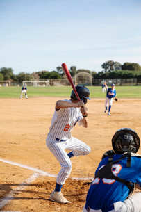 Baseball player at bat on sunny fieldの写真素材 [FYI02337150]
