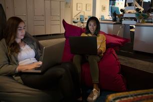 Businesswomen using laptops, working late in office loungeの写真素材 [FYI02337162]