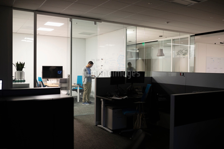 Businessman working late, using laptop in conference roomの写真素材 [FYI02337186]