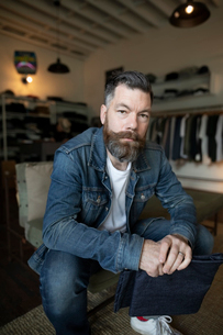 Portrait confident male business owner holding jeans in menswear clothing shopの写真素材 [FYI02337218]