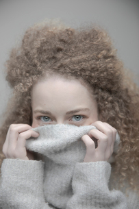 Portrait playful beautiful young blonde woman with curly long hair hiding in sweaterの写真素材 [FYI02337228]
