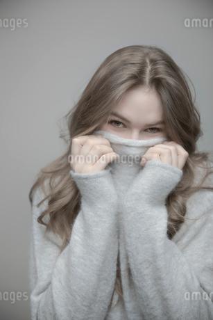 Portrait playful beautiful teenage girl hiding in sweaterの写真素材 [FYI02337283]