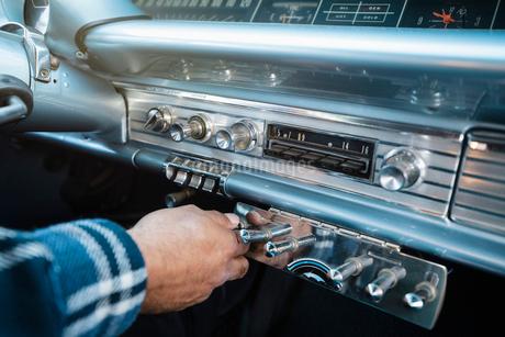 Close up man adjusting dial in low rider vintage carの写真素材 [FYI02337291]