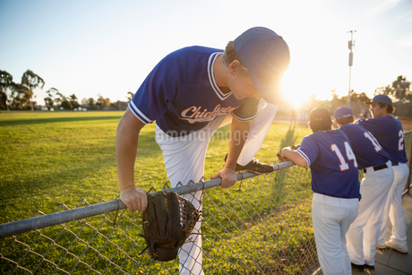 Baseball player climbing over fence on sunny fieldの写真素材 [FYI02337326]