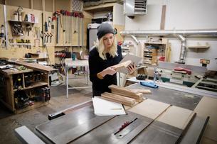 Female carpenter examining cribbage boards in workshopの写真素材 [FYI02337353]