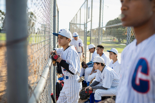 Baseball player watching game behind fenceの写真素材 [FYI02337357]