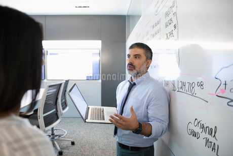 Businessman with laptop leading conference room meeting at whiteboardの写真素材 [FYI02337380]