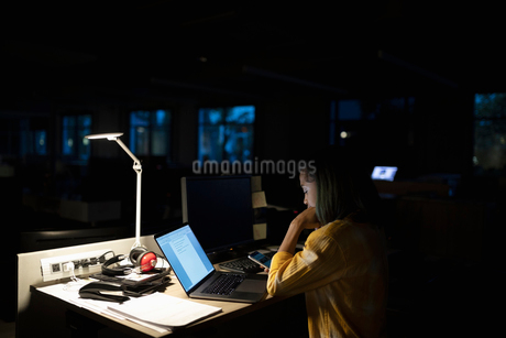 Dedicated businesswoman working late at laptop in dark officeの写真素材 [FYI02337391]