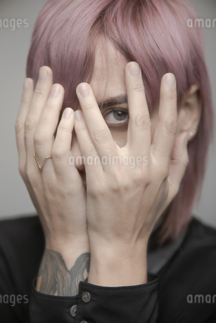 Portrait beautiful non-gender person with pink hair hiding head in handsの写真素材 [FYI02337411]