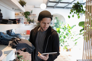 Male business owner with digital tablet arranging display in menswear clothing shopの写真素材 [FYI02337459]