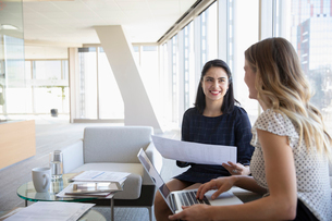 Businesswomen with paperwork and laptop in officeの写真素材 [FYI02337471]