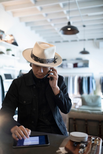 Male business owner using digital tablet and talking on mobile phone in menswear shopの写真素材 [FYI02337485]
