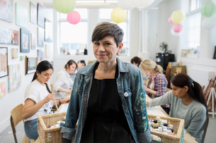 Portrait smiling woman leading art class in community centerの写真素材 [FYI02337494]