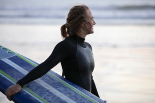 Female surfer in wet suit holding surfboard on beachの写真素材 [FYI02337518]