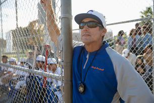 Focused baseball coach leaning on fenceの写真素材 [FYI02337558]