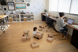 Toddler daughter playing with Christmas gifts on floor behind mother working at laptop in studioの写真素材 [FYI02337602]
