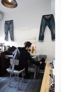 Male tailor working in denim repair shopの写真素材 [FYI02337607]