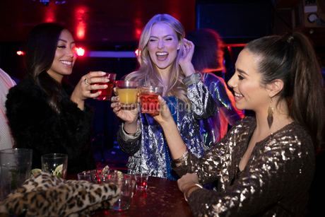 Young women friends toasting cocktails in nightclubの写真素材 [FYI02337627]