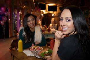 Portrait confident women friends eating at late night dinerの写真素材 [FYI02337637]