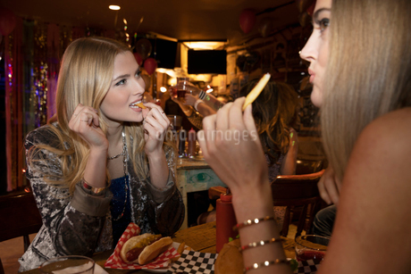 Women friends eating at late night dinerの写真素材 [FYI02337651]