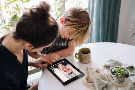 Mother and son using digital tablet at tableの写真素材 [FYI02337654]