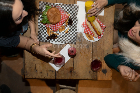 View from above women friends eating hamburger and hot dog in dinerの写真素材 [FYI02337657]