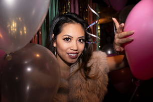 Portrait confident young woman with balloons at partyの写真素材 [FYI02337661]
