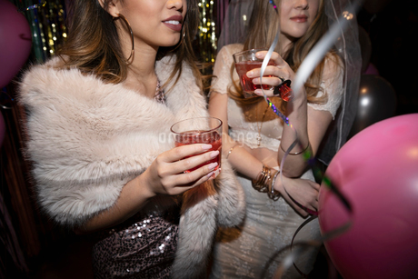Bachelorette and friend drinking cocktails at partyの写真素材 [FYI02337662]