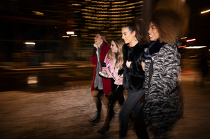 Bachelorette and friends walking on urban street at nightの写真素材 [FYI02337665]