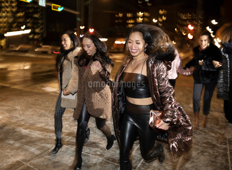 Carefree young women friends crossing urban street at nightの写真素材 [FYI02337668]
