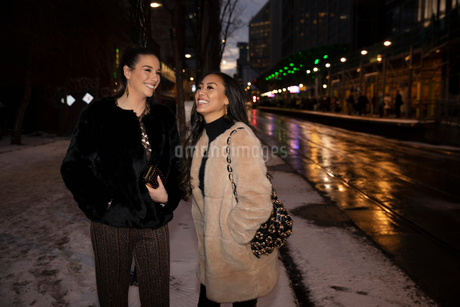 Women friends on snowy urban street at nightの写真素材 [FYI02337672]
