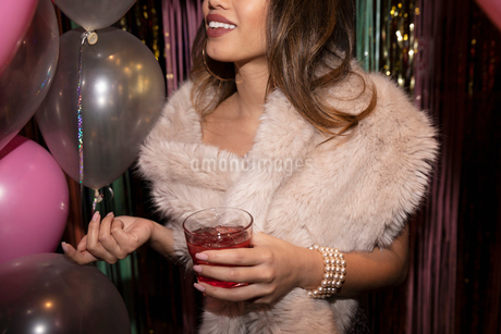 Young woman drinking cocktail at partyの写真素材 [FYI02337683]