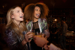 Laughing young women friends drinking in nightclubの写真素材 [FYI02337692]
