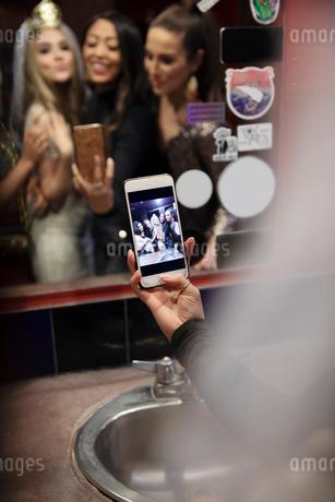 Bachelorette and friends taking selfie in nightclub bathroom mirrorの写真素材 [FYI02337696]