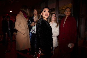young women friends waiting in nightclub queueの写真素材 [FYI02337702]