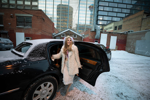 Portrait confident bachelorette getting into limousine in snowy urban parking lotの写真素材 [FYI02337715]