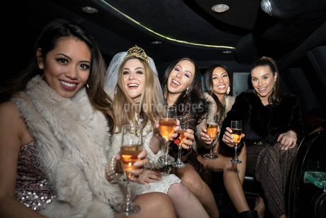 Portrait confident bachelorette and friends drinking champagne in limousineの写真素材 [FYI02337719]