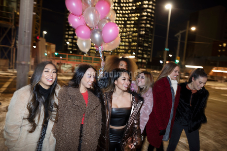Women friends with balloons walking on urban street at nightの写真素材 [FYI02337723]