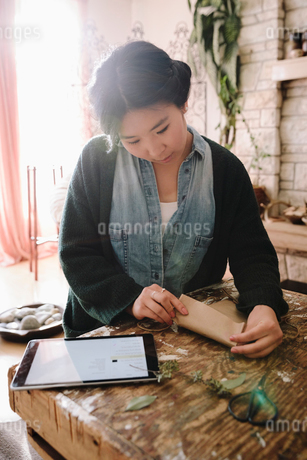 Creative female artist with digital tablet wrapping packageの写真素材 [FYI02337727]