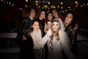 Portrait confident bachelorette and friends on urban street at nightの写真素材 [FYI02337731]