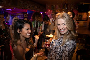 Portrait confident young women drinking in nightclubの写真素材 [FYI02337732]