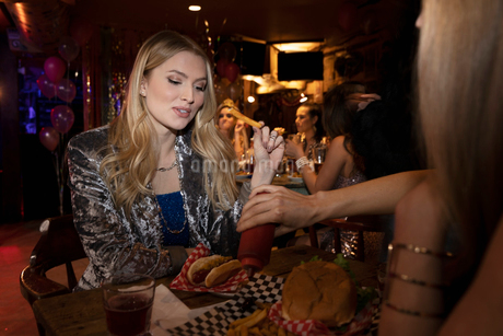 Women friends eating in nightclubの写真素材 [FYI02337736]