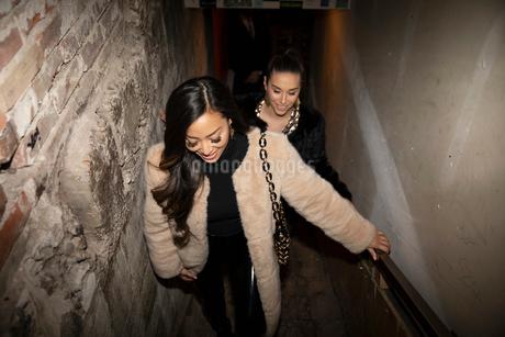 Women friends ascending nightclub stairsの写真素材 [FYI02337741]