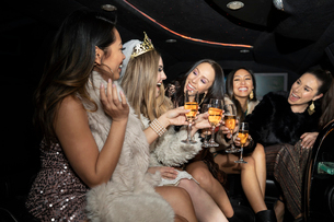 Bachelorette and friends drinking champagne in limousineの写真素材 [FYI02337744]