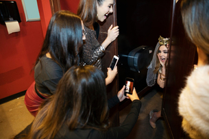 Friends with camera phones photographing bachelorette in bathroom stall in nightclubの写真素材 [FYI02337748]